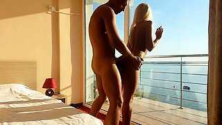 Slender blonde beauty has sex with her lover by the window