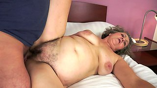 Fat granny is licking a young cock on the bed in this video