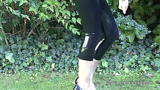 Buxom lady takes erotic poses right on the lawn in her PVC clothing