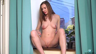 Seductive babe Milana M is masturbating on the windowsill